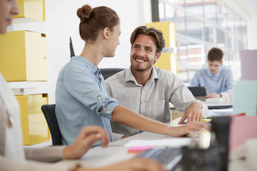 Young man and woman talking in an open plan office
