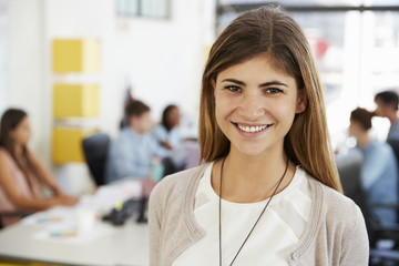 Mid adult white woman smiles to camera in open plan office