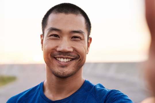 Athletic Asian man taking a selfie during a morning run