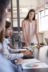 Woman stands addressing colleagues at meeting, vertical