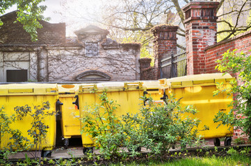 yellow dumpster standing on an inner yard