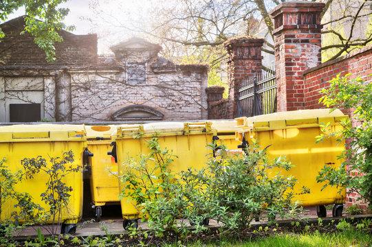 yellow dumpster standing on an inner yard