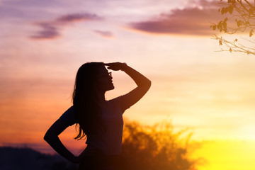 Young woman relaxing in summer sunset sky outdoor.