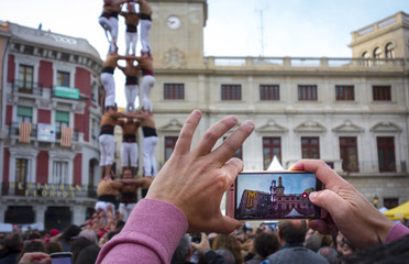 Hand held smartphone taking a picture of Castells Performance