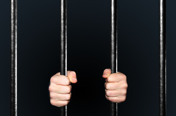 Hands holding Jail Bars