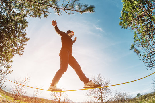A man, aged with a beard and wearing sunglasses, balances on a slackline in the open air between two trees at sunset