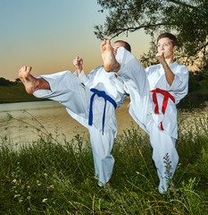 Athletes with red and blue belts are trained karate near the river