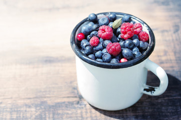 Berries of ripe juicy bilberry and  raspberries in an iron mug on a wooden table.