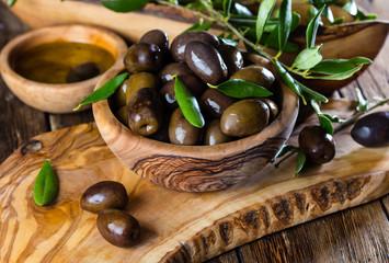 Olives and olive oil in olive wooden bowls