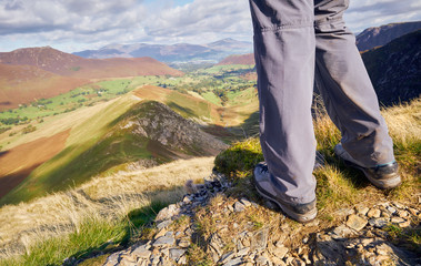 A close up of hikers legs looking down High Snab Bank and Scope Beck in the Lake District, England, UK.