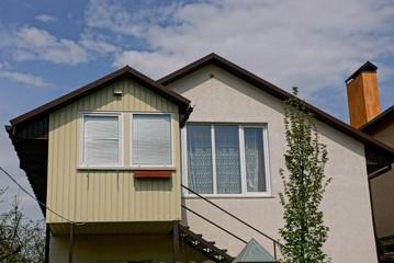 Фасад частного здания с окнами и верандой