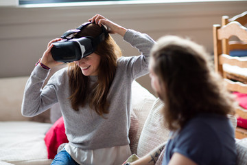 Young adult female putting on VR headset