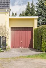 Rotes Garagentor mit gelber Fassade