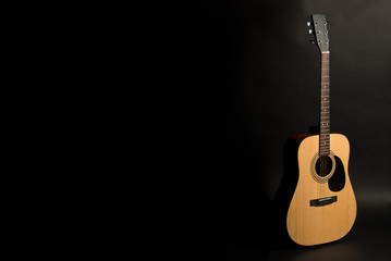 Acoustic guitar on a black background on the right side of the frame, half-turn. Stringed instrument. Horizontal frame.