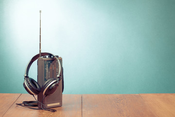 Retro old radio receiver and headphones on mint green background