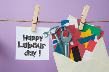 Happy Labour day on 1 may. Hammer and wrench, flags of different countries in the envelope - grunge abstract image