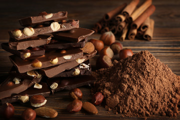 Chopped chocolate bars with nuts and cocoa powder, closeup