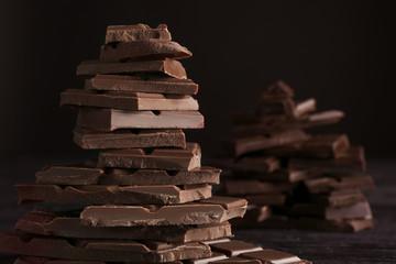 Fototapete - Chopped chocolate bars on dark background, closeup