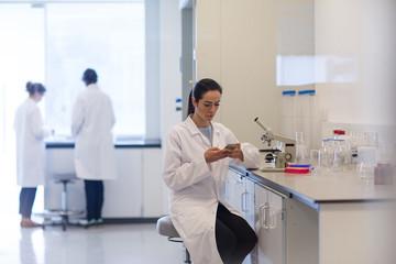 Female scientist using smartphone in laboratory