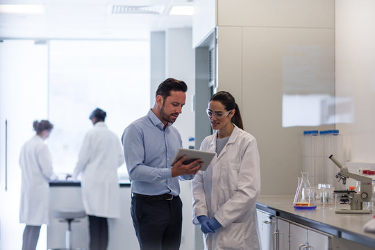 Female scientist discussing data with pharmaceutical sales rep