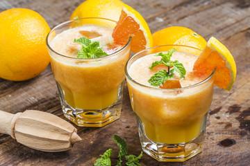 Fresh orange juice, mint and ice on dark background, top view