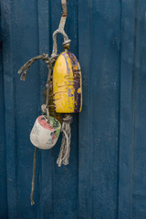 Colorful fishing floats hanging on a wall of metal container