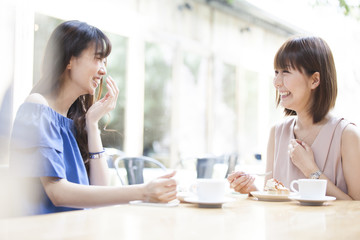 The two ladies are having fun chatting with a bright cafe