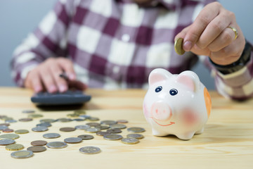 money, home, finance and relationships concept -man with pig bank sitting on desk,Businessman putting coin into the piggy banks,vintage color morning light