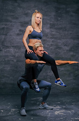Sporty male doing squats with slim fit female on his shoulders.