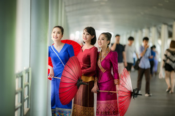 Asian Beautiful Laos woman holding red umbrella traveling skyline Sathorn Modern Building Landmark in Bangkok Thailand.