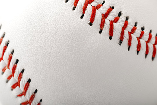 Macro image of a baseball with the closeup on the stitches with copy space