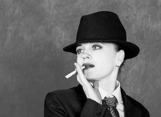 Young woman in manly style with mini cigar on gray background, girl in man's suit and tie, white shirt and hat