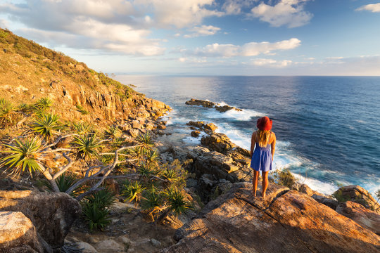 A young woman admires a coastal view over the ocean at sunrise near Coffs Harbour, Australia.