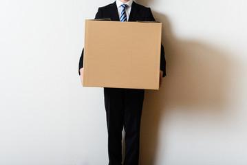ダンボール箱を運ぶビジネスマン