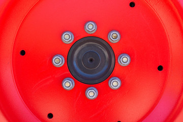 Red wheel hub abstract with shiny nuts.