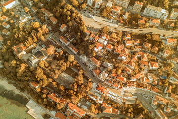 Top view of the city streets with red roofs of houses and highways. Toned