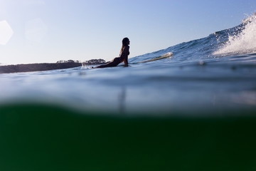 A surfer is back lit by the evening light as she paddles over a cresting wave.