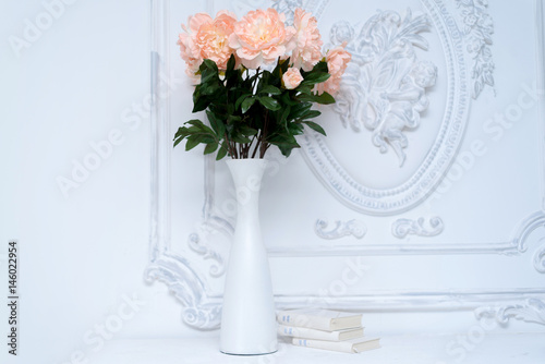 Artificial Pink Peonies In A White Vase Next To White Books