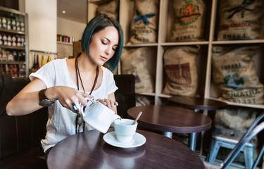 Jeune femme sert une tasse de thé dans un bar