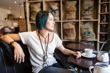 Jeune femme assise devant une  tasse de thé dans un bar