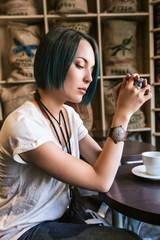 Jeune femme devant sa tasse de thé,pensive, le regard vers le bas
