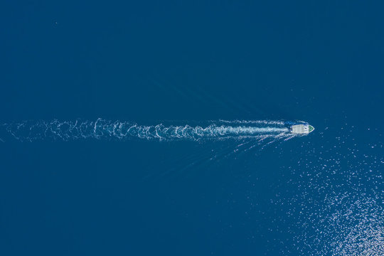 Top view of a white boat sailing to the blue sea