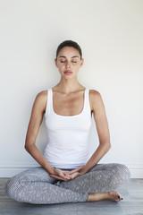Meditating beauty sitting on floor