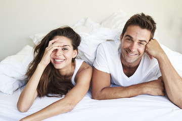 Happy couple lying and grinning in bed, portrait