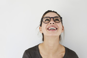 Carefree girl in spectacles, looking up