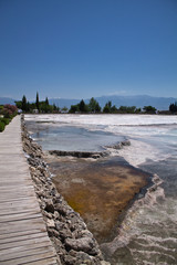 walking on wooden pathway sightseeing of beautiful limestone hot natural turquoise springs in cotton castle, pammukale, turkey