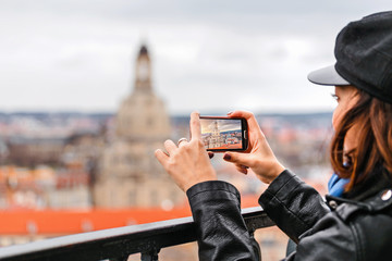 Young woman taking a photo on her smartphone of a Dresden city with Frauenkirche landmark
