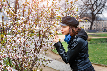 Woman in cap and leather jacket with cherry flowers in spring park