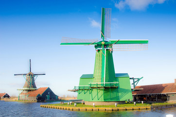 Scenic picture of the water and windmills in Zaanse Schans, Holland, Europe against the backdrop of a cloudy sky.