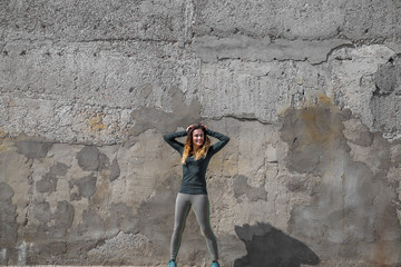 fitness girl in sport clothes on wall background